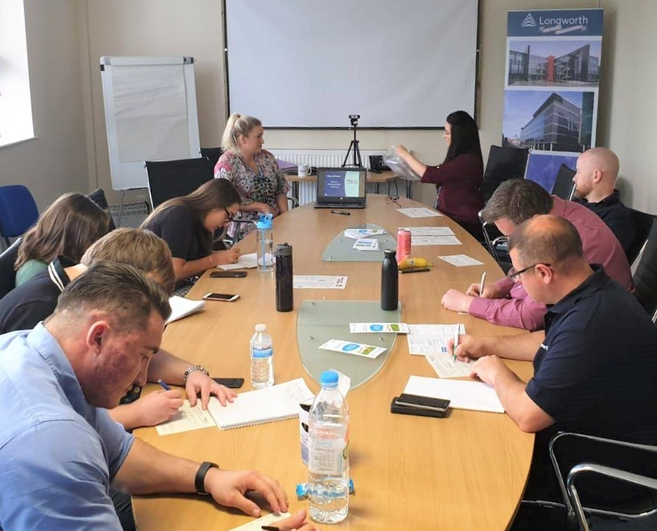 Longworth board room training photo. Staff sat around large meeting room table