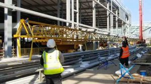 Crane with long lifting beam to lift roof panels onto roof