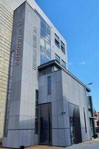 Grey coloured cement board clad entrance to building. RCI Magazine Facade Awards 2021!